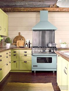 Celadon cabinetry pairs playfully with the aqua enameled range in this casual cottage kitchen. The green hue connects the room with nature while emphasizing a fun, laidback style. Balance the painted cabinets with a light, neutral wall color, and reserve wood or dark tones for flooring. Paint Color:Valspar for Lowe's, La Fonda Olive, 6006-6B.