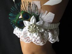Bride's Wedding Garter is gathered in white satin and pearled lace ruffle. Graced at the center with satin white Kanzashi flower with sparkle rhinestone center, spray of white marabou and coque feathers, Peacock Eyes and curly sword feather. set/ one only $79.99 matching fascinator available as well for extra