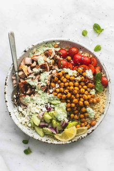 Healthy and hearty Greek Chicken Power Bowls are loaded with savory chicken, quinoa, roasted chickpeas, cucumber salad, tomatoes, and creamy tzatziki.