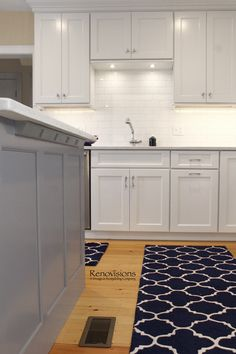 A completed kitchen remodel by Renovisions. Kitchen remodel, shaker cabinets, white painted cabinets, grey cabinets, contrasting island, kitchen island, cabinet storage, pantry cabinet, quartz countertop, Silestone countertop, deep drawers, wood floor, wood flooring, subway tile backsplash.