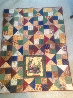 A quilted throw made using the Missouri Star Quilt Company tutorial for the Alter Ego Quilt with modifications (used scrappy fabric and added a panel).