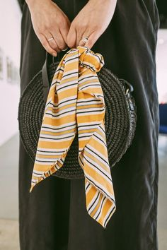 A yellow scarf to add a pop of colour to an all black outfit.