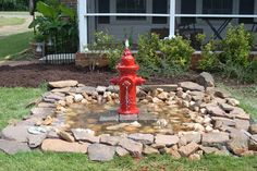 "Fire Hydrant Water Feature -- ""This is a water feature we created from a fire hydrant. The top was drilled out on a drill press to allow for the tubing. The pond is 7'x7' with a 45 mil. thick liner  500 gph pump. It's filled with rocks to make ""puddles"" for the birds to play in"".  -Diane Kitchen"