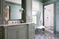 Chic bathroom features a gray cabinets fitted with a gray washstand topped with white quartz fitted with a sink and polished nickel faucet placed under gray framed mirror lit by Vivian Single Sconces flanked by cabinets.