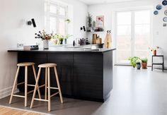 Køkken med elementer i sort træ, med sort bordplade, gråt linoleumsgulv og barstole i lys træsort