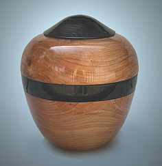 This handcrafted urn is made from cherry or maple wood. It is one solid piece of wood, plus the lid.  The lid and stripe are finished in black lacquer. The urn is a signed original and one of a kind.  It is sealed with an advanced urethane finish, enhancing its durability and preserving the wood. Find it at http://artisurn.com/collections/wooden-urns/products/cherry-or-maple-urn #urn #cremation #handcrafted