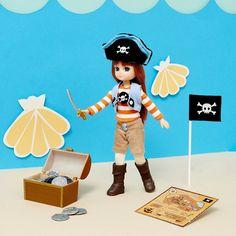 Lottie, la reine pirate - SuperHero-Girls  La poupée Lottie, Reine Pirate et ses accessoires : coffre au trésor contenant 8 pièces d'argent, une carte au trésor, un drapeau de pirate