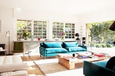 Eclectic, modern living room with blue sofas and wood coffee table