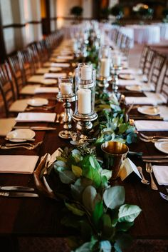 wedding reception  detail featuring lush garland of lemon leaf and seeded eucalyptus, pillar candles, mercury glass, brass vases and antlers set on varnished wood farm style tables.