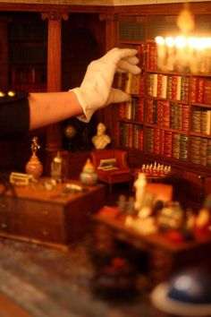Filing a Tiny Book in the Library of Queen Mary's doll house at Windsor Castle