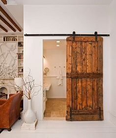 The Brooklyn Home Co.    Guest bath with reclaimed wood sliding barn door. LOVE!