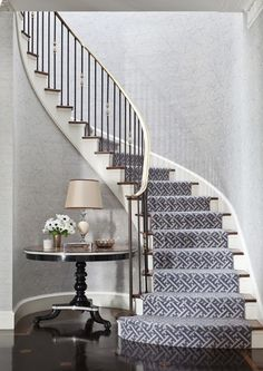 Gorgeous stairway by Markham Roberts. Textural gray wallpaper, grey graphic key runner contrasts it's sharp edges with the graceful swoop on the staircase, and don't miss the dark inlaid floors. Foyer Staircase, Staircase Runner, Curved Staircase, Entry Hallway, Stair Railing, Staircase Design, Railings, Railing Ideas, Design Entrée