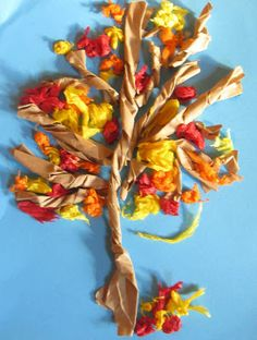 AUTUMN TREE ART light blue or dark blue cardstock paper for their background. twist long strips of 2 inch wide brown paper into the tree trucks and branches.   cut the strips for the smaller branches. add leaves to the trees, scrunched up pieces of red, green, yellow and orange tissue paper.