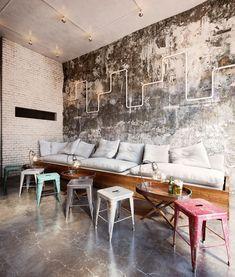 Tolix stools, padded bench seating, exposed lighting, acid washed walls, polished concrete floors.
