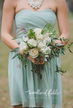 organic and loosely tied bridesmaid bouquet of vendela roses, white stock, white lisianthus, white queen anne's lace, seeded eucalyptus, dusty miller, fern, jasmine trails, white fountain grass, and succulents wrapped in cream satin ribbon