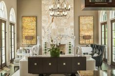Mirror image artwork[C] lamps[C] chests and accents create a contemporary display[C] and allow for the Borealis Travertine floor to ceiling fireplace to be the star of this room[P] Glam Living Room Design