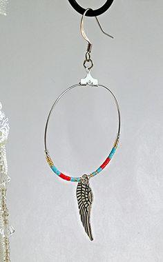 Ces boucles d'oreilles sont composées d'apprêts, crochets, de créoles argentées de 4 cm, de perles Miyuki Delicas 11/0 et une breloque en forme d'aile