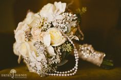 Instead of the typical flower bouquet, try this one on for size; it's a combination of draped pearls, sparkling brooches, pearl flowers, sola flowers, velvet leaves and fresh roses, dusty miller, and seeded eucalyptus.