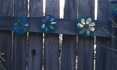 Paint flower patternsp on old cds glue on some fishing line and hang on your fence.