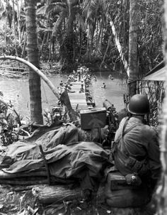 A machine gunner watching for snipers as an engineer crew bathes in the river below, Guadalcanal 1943