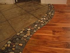 River rock in between wood and tile floors. Love this creative idea for the transition between types of flooring.maybe from the bathroom into the next roo. :-)