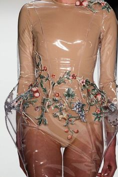 Model walks on runway in nude long-sleeved bodysuit under clear vinyl sculptured dress with embroidery.. DIY the look yourself: http://mjtrends.com/pins.php?name=clear-vinyl-for-dresses