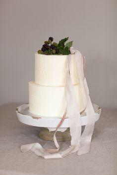 #white two tier cake with berry topping and ribbon