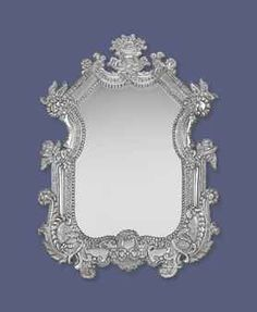 A SPANISH OR PORTUGUESE COLONIAL STYLE SILVER MIRROR EARLY 20TH CENTURY Cartouche form, embossed and chased with scrolling foliage, shells, flowers and leaves, surmounted by a cartouche, with mahogany back, marked near base 45 in