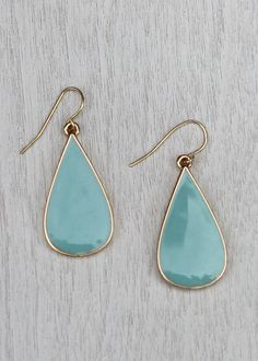 With a  shape like a raindrop  these 2 tone epoxy earrings feature an aqua color on one side and a dove grey on the other. The earrings are trimmed in gold. Measures 1 1/2 including hook. $20.00