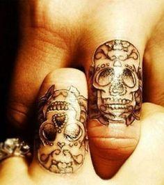 Uma tatuagem de casal em forma de caveira nos dedos