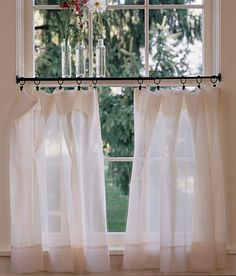 Thinking of doing a half/tiered curtain in living room. Like the idea of using drapery hooks so the window can be opened easily in the morning with tiebacks. Wondering if they are using a tension rod, really like the style.