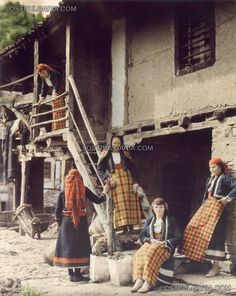 Girls in the Rhodope costumes pose for an old house, 1932