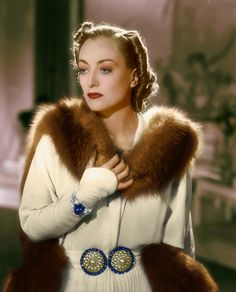 Joan wears a glamorous fur trimmed outfit from a movie from the 1930's.