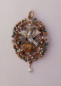 Dove Pendant 1550 . This pendant, an ornament for the neck or the bust, displays the lightness and delicacy of its openwork design. Its oval band of gold is decorated with leaves in green enamel, gold berries, white flowers, seven of which contain a ruby.