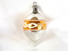 This vintage Poland Christmas ornament is a small teardrop. It is silver with a gold band around the middle.