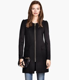 Straight-cut coat in a woven, textured fabric with slightly puffed sleeves. Concealed front zip, side pockets, and one inner pocket. Lined