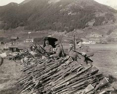 With the final capitulation of Germany to the Allies, German soldiers who have bore arms for over five years against almost all of Europe and the U.S., surrender their Mauser 98k rifles to their American forces near Landeck, Austria. They seem quite pleased to have survived, and that it is all over. Hand grenades and other small arms and equipment can be seen piled up beyond the rifles. Photographed by Brigadier General Charles Day Palmer