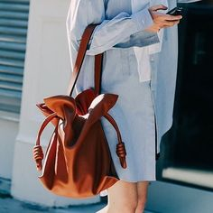 The Loewe Flamenco handbag has been named summer's top travel bag by Vogue Paris. The supple two-fold design and drawstring top is made ever more elegant with a T-bar profile and hand-painted edges.