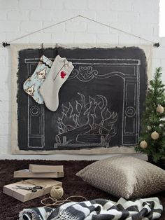 Cozy Up By the (Faux) Fire No mantel? No worries — Santa will be sure to stuff your stockings when they're hanging from this clever faux-mantel wall hanging made from a drop cloth, drapery hardware and chalkboard paint.