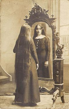 Victorian girl looking in a mirror, love her hair. And very interesting expression.