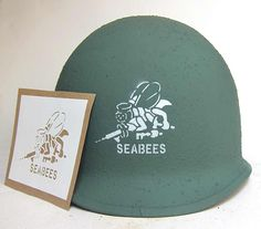 Rare helmet stencil for the famous 'SeaBees' - it features a 'Bee' and machine gun. 'SEABEES' comes from the term Construction Battalions.  The need for a militarized Naval Construction Force to build advance bases in the war zone was evident when under international law civilian engineers could be executed if they resisted military forces. The SeeBees were thus formed.   http://www.warhats.com/ww2-american-stencils.html   www.warhats.com