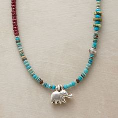 """ELEPHANT CHARM NECKLACE -- Hill tribe artisans coax from Thai silver a delightful elephant bearing good luck in his upturned trunk. Rubies, gaspeite, sugilite and silver beads enrich the turquoise strand. Handmade in USA. Coral droplet at lobster clasp. 17-1/2"""" to 19""""L."""