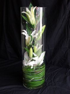 b4eee9335fc Lily grass in the bottom and white lilies down in the clear glass vase.