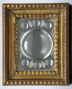 Italian gilt wood cut-glass mirror with both convex and concave  surfaces, stylized flowers in the corners and small cut-diamond elliptical designs.      Italian Circa 1830     Height: 11"