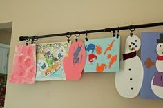 A great idea for hanging kids artwork!  A curtain rod w/ clips to rotate their work.  Love this.