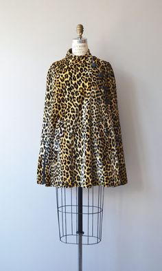 Vintage 1960s faux leopard cape with short funnel collar, asymmetrical glass buttons, pockets, split openings for both arms and black acetate lining.  --- M E A S U R E M E N T S ---  fits like: fits most bust: free waist: free hip: free length: 31 brand/maker: n/a condition: excellent  ★ layaway is available for this item  ➸ More vintage coats http://www.etsy.com/shop/DearGolden?section_id=5800175  ➸ Visit the shop http://www.DearGolden.etsy.com _...