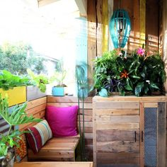 Everything in this tropical islands style outdoor room is a DIY with pallets! From living wall, furniture, to stenciled wood floor!