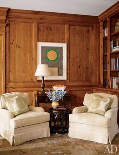 In the library of a Lake Forest, Illinois, home designed by Timothy Corrigan, a Jasper Johns print hangs above a McGuire drum table and Monte Allen armchairs covered in a Kravet fabric | archdigest.com