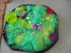 """Christine has used green shredded packing material with chicks, fabric flowers & plastic eggs filled with rice, or pasta inside to make different sounds - from http://bubble-and-balloons.blogspot.co.uk ("""",)"""