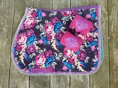 Stunning floral print English Saddle Pad in the colors purple, pink, cream, grays and blues. This pad has a solid blue under color and is filled